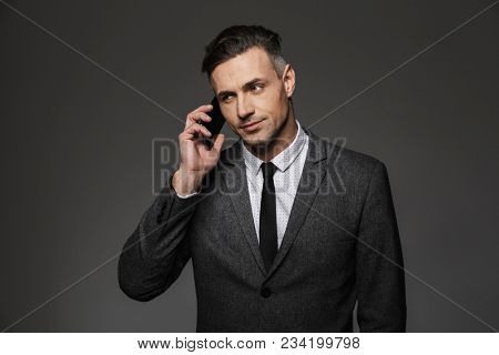 Image of serious man employer dressed in business costume having mobile talk in office isolated over gray background