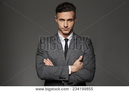 Image of mature unshaved man wearing business suit looking on camera with strict determined gaze isolated over gray background