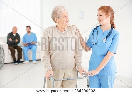 Senior woman with walking frame and young caregiver at home