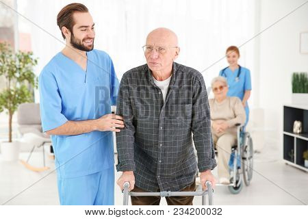 Senior man with walking frame and young caregiver at home