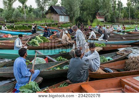 Srinagar, India - June 16, 2017: Unidentified vegetable sellers taking their produce to the floating market  early in the morning on Dal Lake in Srinagar, Kashmir.