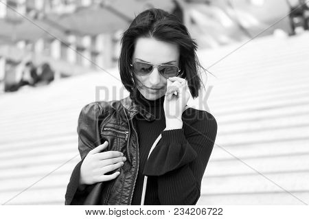 Woman In Sunglasses On Stairs. Girl With Brunette Hair In Black Clothes. Ambition, Challenge, Succes