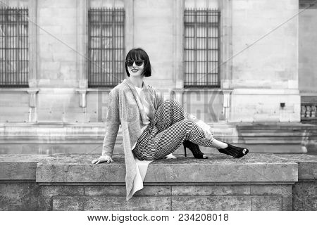 Woman Smile With Red Lips In Sunglasses, High Heel Shoes, Fashionable Clothes On Stone Fence On Hous