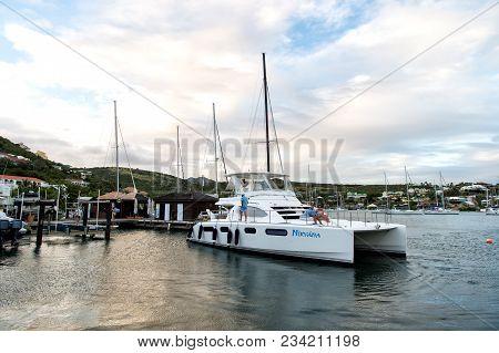 Philipsburg, Sint Maarten - January 24, 2016: Yacht Anchored At Sea Pier. People Sit On Modern Ship