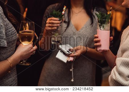 Women Drinking Cocktails And Wine And Talking With Guests On The Party Event