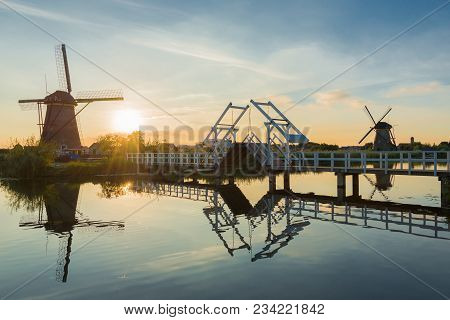 A Landscape In The Netherlands With Two Windmills And A Drawbridge In The Low Sun At The End Of A Su