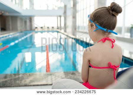 Rear View Of Calm Pensive Girl Wearing Swimsuit And Goggles Sitting In Armchair And Contemplating Wa