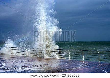 Huge breaking stormy wave. Big wave. The big wave is breaking about the shore. Rainbow