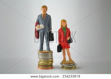 Stack Pile Of Coins With Miniature Man And Woman. Gender pay discrimination concept. wage Disparity