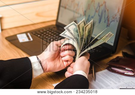A Man In A Suit Counts The Money On A Laptop With Economic Graphs. Investments In Real Estate. Busin