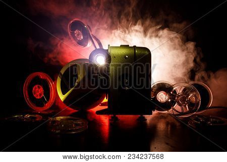 Old Style Movie Projector, Close-up. Film Projector On A Wooden Background With Dramatic Lighting An