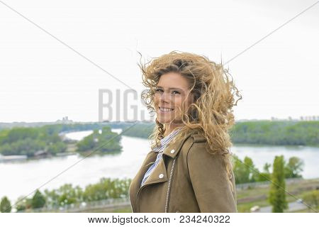Beautiful Long Haired Woman Enjoying The Landscape View On A Windy Cloudy Day