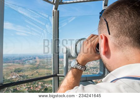 Young Man Tourist Looking Through Telescope On Top Of Avala Observation Tower Deck, Belgrade, Serbia