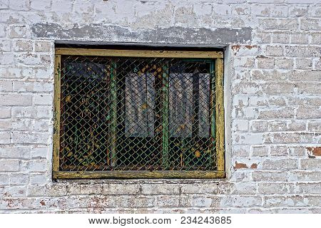 Old Iron Window With A Lattice On A Gray Brick Wall