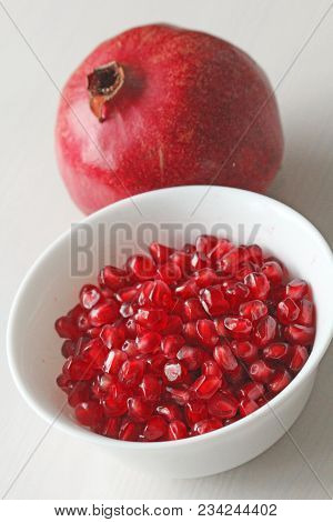 Grains Of Red Ripe Pomegranate Lie In A White Bowl. Big Ripe Red Granets Or Garnets. Fruits Of Red R