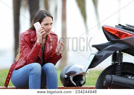 Portrait Of An Angry Biker Calling Insurance Beside A Motorbike Outdoors In The Street