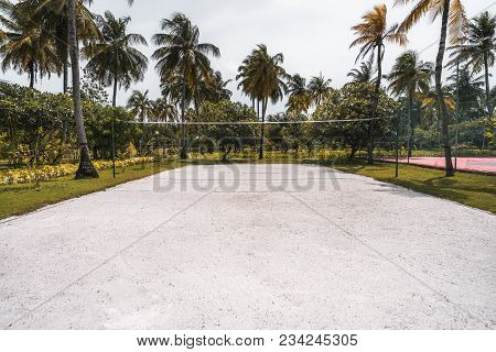 Wide-angle Frontal View Of The Volleyball Court: Coral Sand On The Ground, Multiple Palm Trees And O