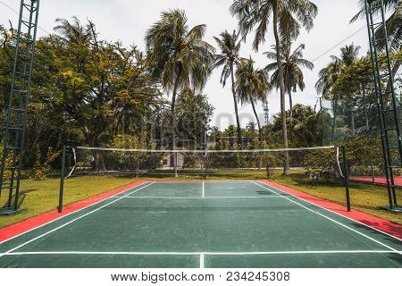 Wide-angle Frontal View Of A Cozy Badminton Court On A Summer Day: Red And Green Field With Marking