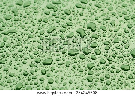 Green Drops Of Rain Or Water Drop On The Hood Of The Car. Rain Drops On The Surface Of The Car Or On