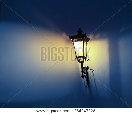 Soft focus. Decorative street lamps. Shadow and light on the wall