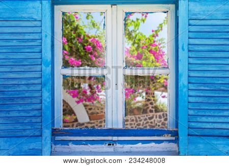 Beautiful vintage Greek window with blue shutters on a white wall. Typical Greek picture with wild cat.