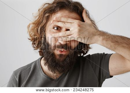 Impatient Good-looking Eastern Guy With Curly Hair And Beard Covering Eyes With Hand And Peeking Thr