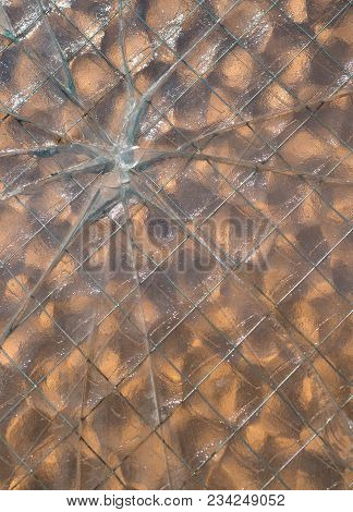 A Bullet Hole Through Wire Mesh Glass With Glass Breaks In A Star Pattern.
