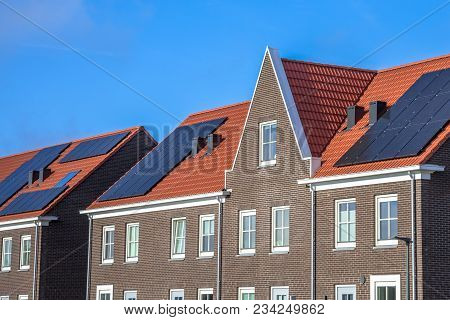Close Up Of Modern Row Houses With Solar Panels, Brown Bricks And Red Roof Tiles In Neoclassical Sty