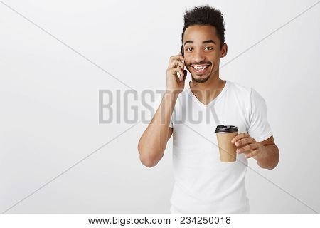 Guy Familiar With Multitasks. Studio Shot Of Pleased Attractive African-american Boyfriend, Drinking