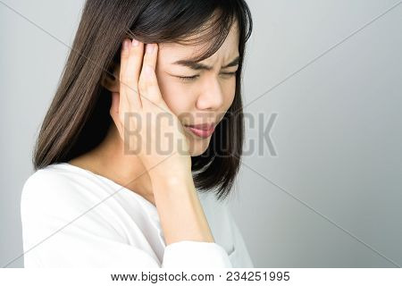 Woman In A White Dress Is Touching Head To Show Her Headache. Causes May Be Caused By Stress Or Migr