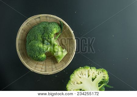 Fresh Broccoli In Basket On Black Background Top View
