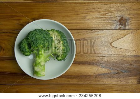 Fresh Broccoli On A White Plate On Wooden Background, Top View