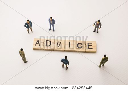 Miniature Figures Businessman : Meeting On Advice Word By Wooden Block Word On White Paper Backgroun