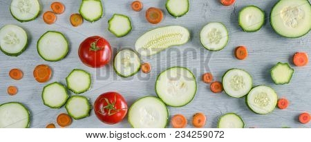 Wide photo vegetables on wooden background. Top view of cucumbers, tomatoes, zucchini, carrots.