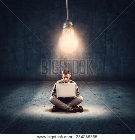 Man Working On Laptop In A Dark Room Illuminated By A Light Bulb. Suggesting The Concept Of Working