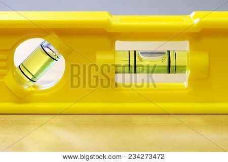 Yellow Spirit Level On Flat Wooden Surface. Close Up Horizontal Image With Space For Text.