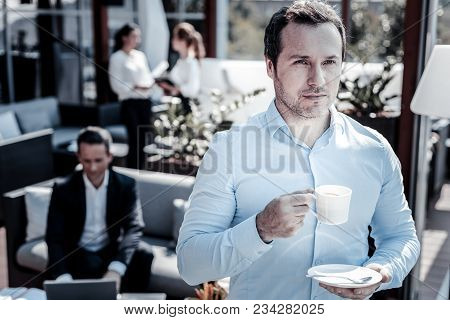 Favorite Espresso. Serious Nice Self Employed Man Holding A Coffee Cup And Looking In Front Of Him W