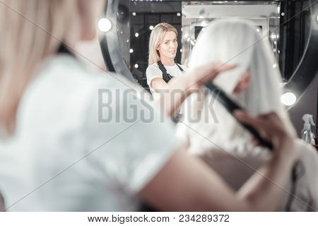 Professional Hairdresser. Nice Smart Professional Woman Looking Into The Mirror And Combing Hair Of