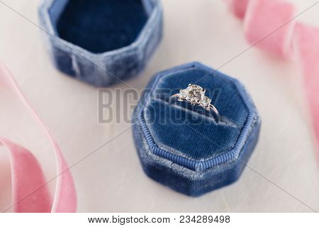 White Golden Wedding Ring With Diamonds In Blue Vintage Velvet Box On White Background With Pink Rib