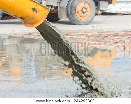 Pouring ready-mixed concrete after placing steel reinforcement to make the road by mixing mobile the concrete mixer. poster