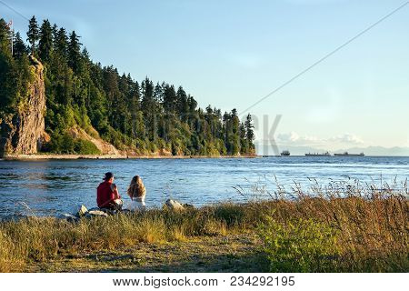 A Young Couple Sits At The Shore Of The Bay, On The Opposite Shore A Wooded Cliff, Blue Sky, Several