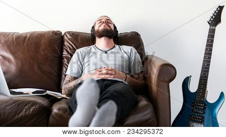 Caucasian man taking a break from work by listening to music stress relief concept