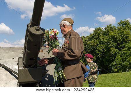 Kiev, Ukraine - May 09, 2016: Veteran Lays Flowers At The Gun In The Park Of Eternal Glory