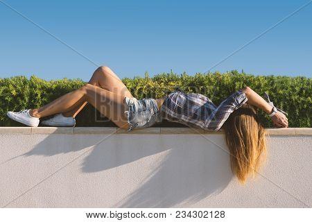 Beautiful Girl Lies Against The Grass Background