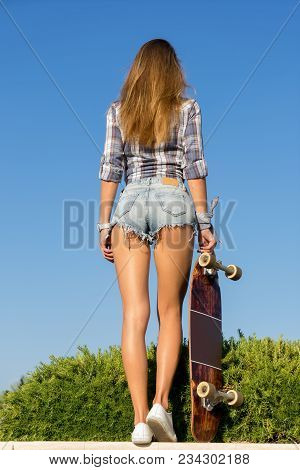 Young Girl Skateboarder With Long Hair In Denim Short