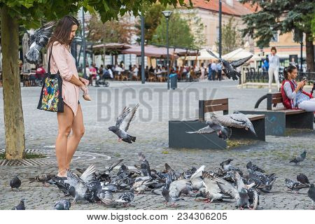 Cluj-napoca, Romania - August 29, 2017: Unidentified Young Frowning Woman With Parrot Print Bag Feed
