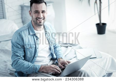 Professional Freelancer. Delighted Cheerful Smart Man Sitting On The Bed And Using His Laptop While