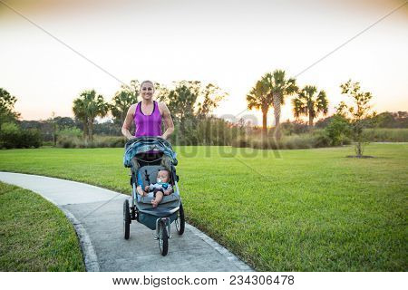 Beautiful, fit woman walking and jogging outdoors along a paved sidewalk in a park pushing a stroller at sunset