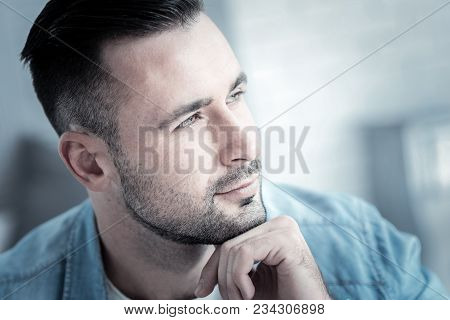 Thoughtful Look. Nice Handsome Young Man Holing His Chin And Looking In Front Of Him While Being Tho
