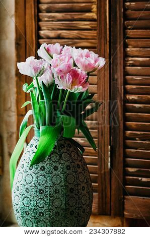 A Soft Focused Bouquet Of Pink Opened Tulips In An Old Big Vase On A Window Sill, Wooden Jalousie In